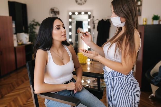 Wizażystka pracuje z modelką w studio urody