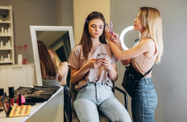 Wizażystka przypięła klientce włosy. kobieta w makijażu zagląda do telefonu.