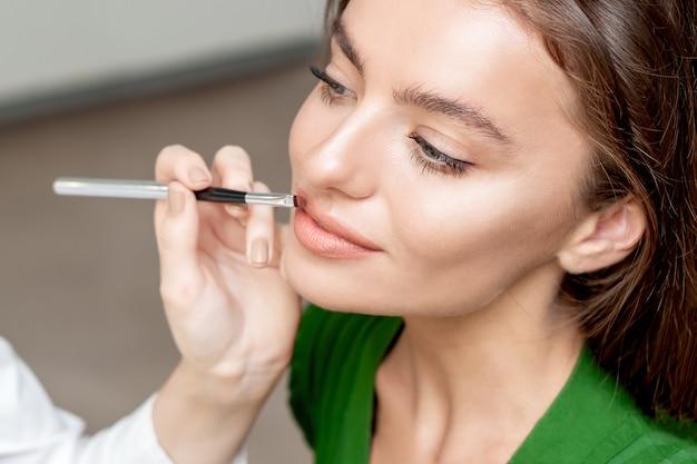 Wizażystka ręka nakładająca szminkę na usta kobiety