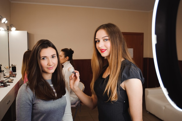 Wizażystka robi profesjonalny makijaż młodej kobiety. beauty shcool.