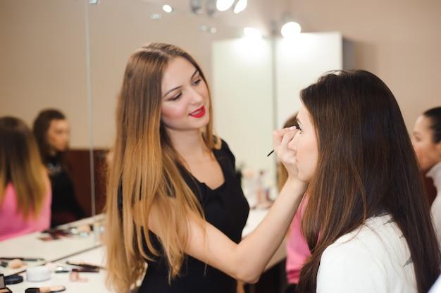 Wizażystka robi profesjonalny makijaż młodej kobiety. shcool piękności
