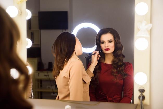 Wizażystka robi profesjonalny makijaż młodej kobiety. szkoła makijażystów