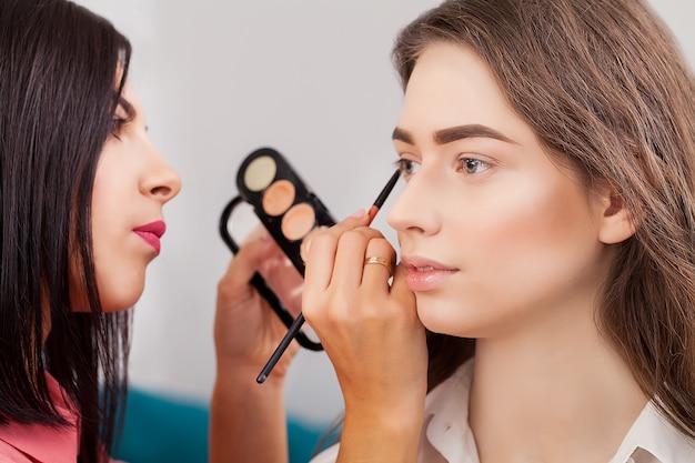 Wizażystka robi profesjonalny makijaż młodej kobiety w pobliżu lustra w studio urody