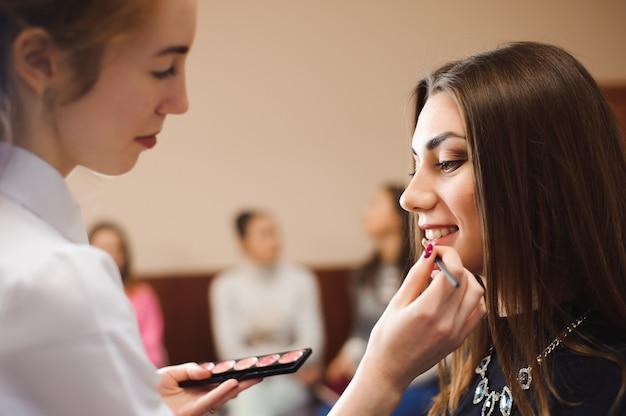 Wizażystka robi profesjonalny makijaż młodej kobiety.