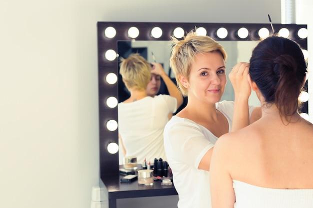 Wizażystka robi profesjonalny makijaż młodej kobiety