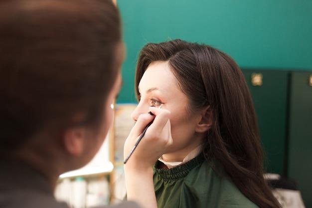 Wizażystka rzuca cień na młodą piękną dziewczynę. ładna dama przyszła do salonu kosmetycznego na zabiegi kosmetyczne