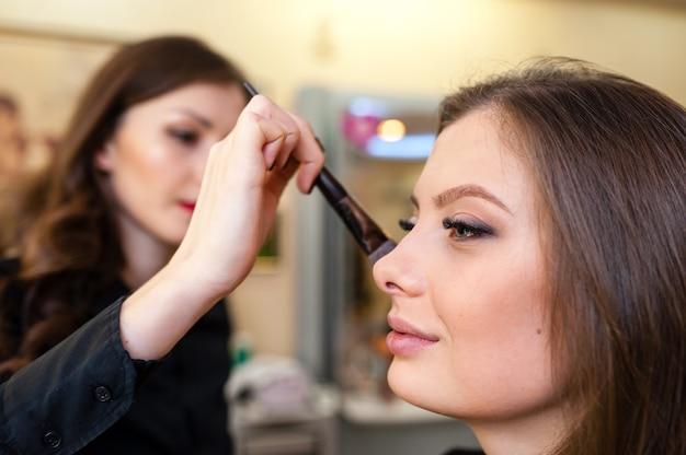 Wizażystka sprawia, że makijaż pięknej dziewczyny