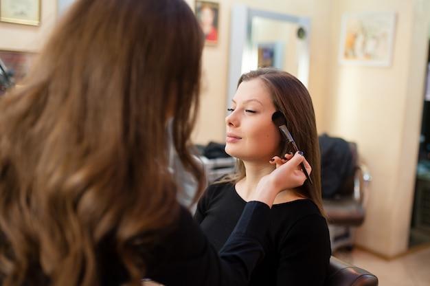 Wizażystka sprawia, że makijaż pięknej kobiety