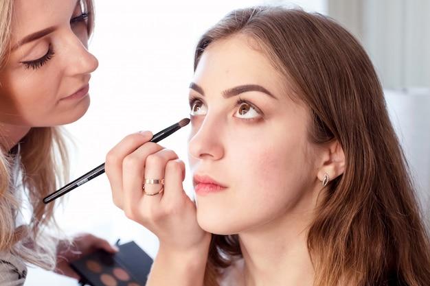 Wizażystka sprawia, że wieczorowy makijaż młodej dziewczyny o brązowych włosach. zwyczajny outfit. za kulisami procesu.