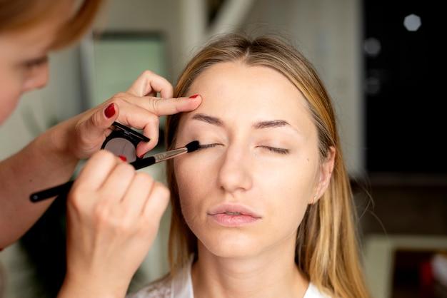 Wizażystka stawia makijaż na twarzy dziewczyny