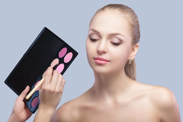 Wizażystka stosowania makijażu oczu dla pięknej kobiety blondynka. cień do powiek