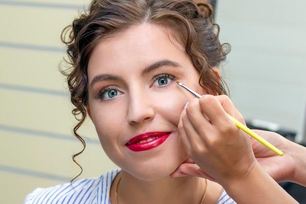 Wizażystka stosuje cień do powiek. piękna twarz kobiety. ręka visagiste, malowanie kosmetyków młodej modelki urody. makijaż w trakcie