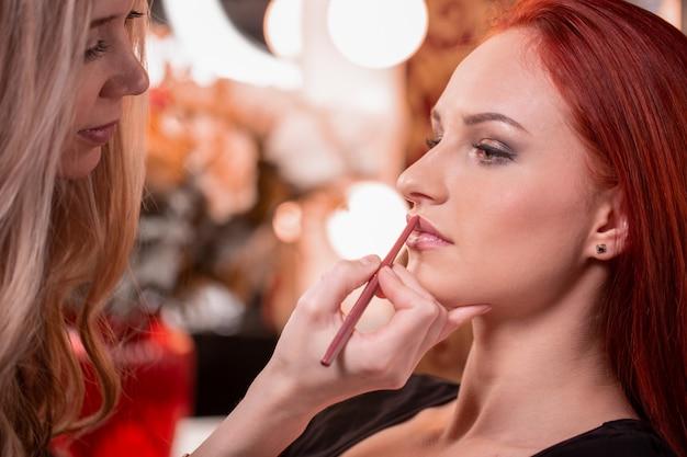 Wizażystka stosuje czerwoną szminkę.