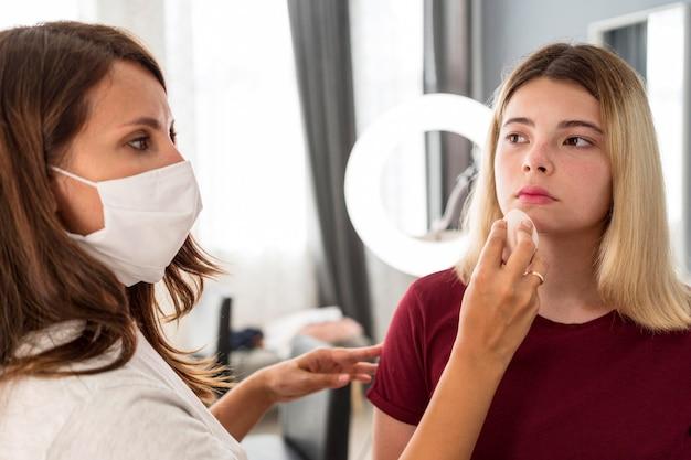 Wizażystka w masce i nakładająca szminkę na klienta