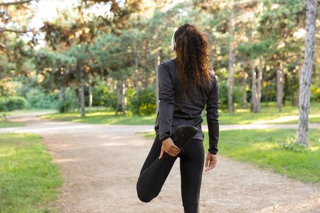 Wizerunek 20-letniej brunetki kobiety noszącej czarną odzież sportową, ćwiczącej i rozciągającej ciało w zielonym parku