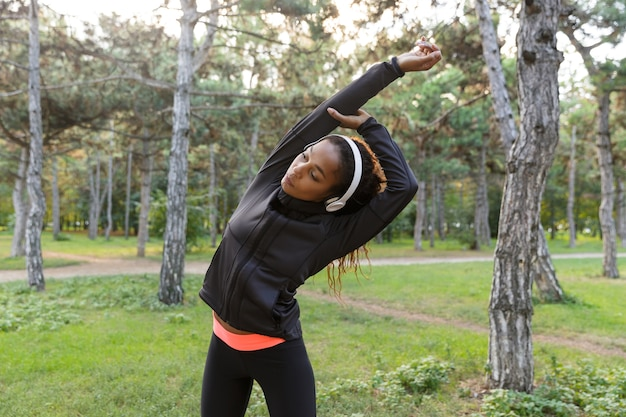 Wizerunek 20-letniej fitness kobieta ubrana w czarny dres, ćwicząca i rozciągająca ciało w zielonym parku