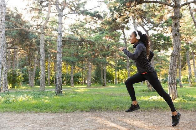 Wizerunek 20-letniej fitness kobieta ubrana w czarny dres i słuchawki, ćwicząca podczas biegania przez zielony park