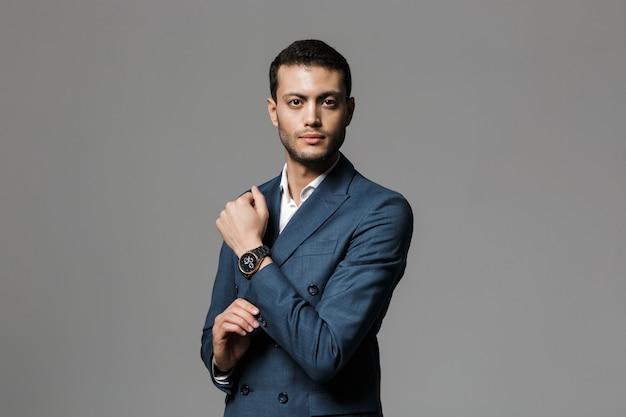 Wizerunek 30s brunetka arabski biznesmen w oficjalnym garniturze i demonstruje zegarek na rękę, odizolowane na szarej ścianie