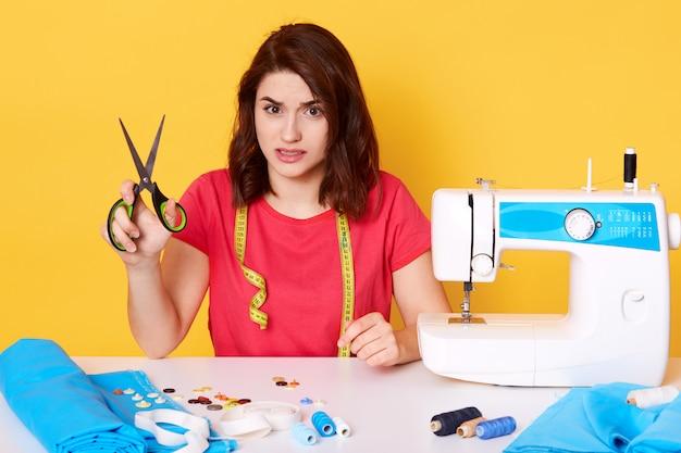 Wizerunek atelier dziewczyna i różni narzędzia w szwalnym warsztacie