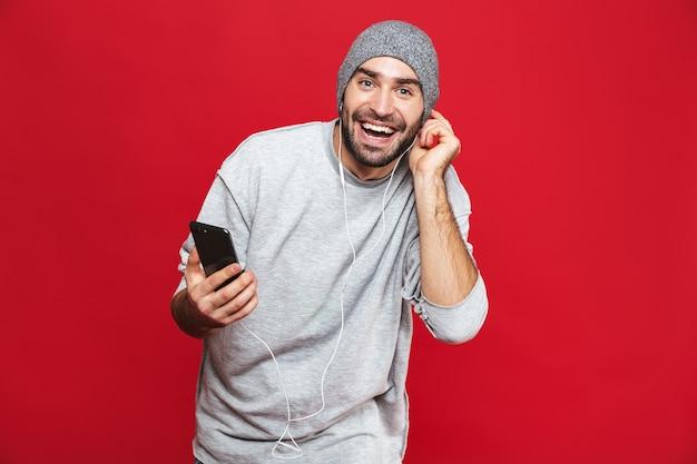 Wizerunek atrakcyjnego człowieka 30s słuchania muzyki za pomocą słuchawek i telefonu komórkowego, na białym tle