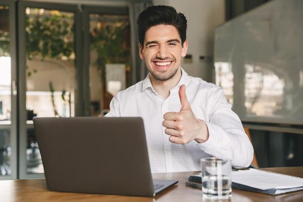 Wizerunek atrakcyjnego uśmiechniętego biurowego faceta 30s ubrany w białą koszulę mrugający i pokazujący kciuk do góry siedząc i pracując na laptopie