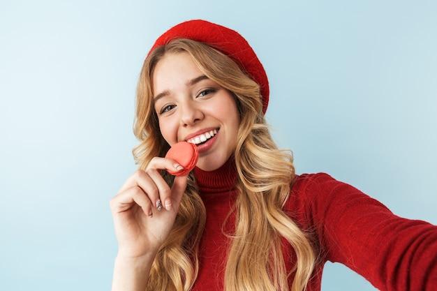 Wizerunek atrakcyjnej blond kobieta 20s ubrana w czerwony beret jedzenie ciastka makaronik podczas robienia zdjęcia selfie, na białym tle