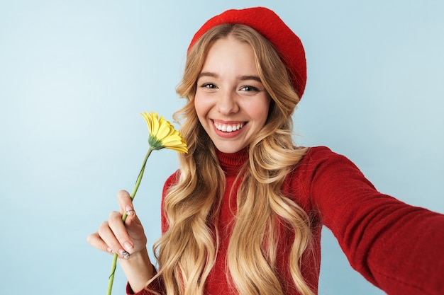 Wizerunek atrakcyjnej blond kobieta 20s ubrana w czerwony beret trzymając piękny kwiat podczas robienia selfie zdjęcie na białym tle