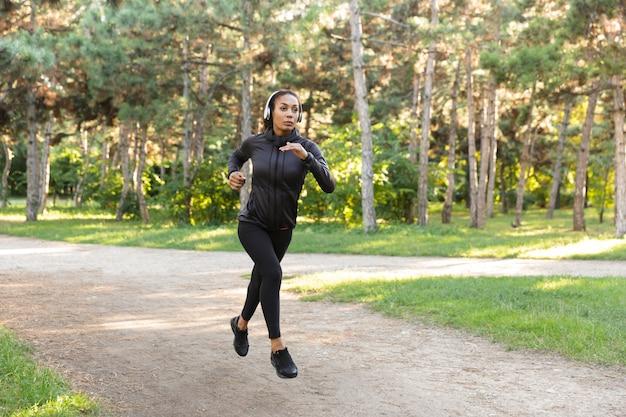 Wizerunek atrakcyjnej kobiety lat 20. ubrana w czarny dres i słuchawki, ćwicząca podczas biegania przez zielony park