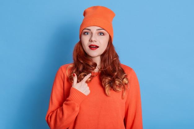Wizerunek atrakcyjnej pani z otwartymi ustami, która kieruje palec na klatkę piersiową, nosi swobodną pomarańczową koszulę i kapelusz