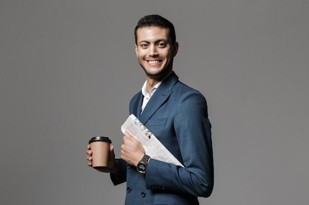 Wizerunek atrakcyjny arabski biznesmen 30s w formalnym garniturze trzymając gazetę i kawę na wynos, odizolowane na szarej ścianie