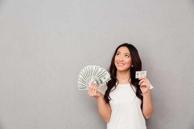 Wizerunek azjata zadowolona kobieta 20s trzyma fan pieniędzy dolarowi banknoty i kredytowa karta i patrzeje na copyspace, odizolowywający nad szarości ścianą