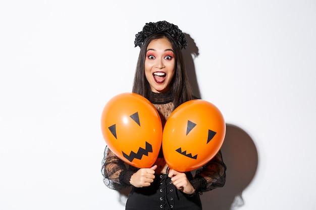 Wizerunek azjatyckiej dziewczyny w stroju złej wiedźmy trzymającej dwa pomarańczowe balony z przerażającymi twarzami, świętującej halloween, stojącej na białym tle.