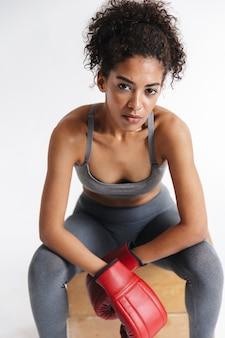Wizerunek beautful młodych niesamowite fitness sport afrykańska kobieta bokser pozowanie na białym tle nad białą ścianą w rękawiczkach.