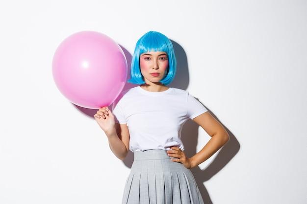 Wizerunek bezczelnej azjatki w niebieskiej peruce, wyglądającej na zdeterminowaną, trzymającej różowy balon, stojącej.