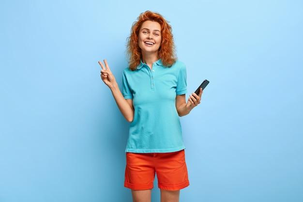 Wizerunek beztroskiej optymistycznej rudej samicy robi gest pokoju, lubi wolny czas
