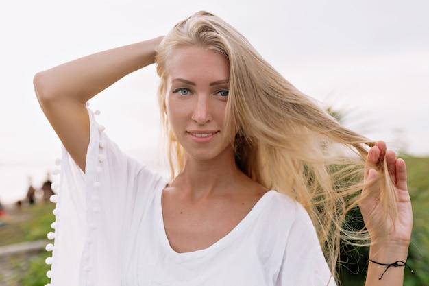Wizerunek beztroskiej uśmiechniętej kobiety w białej bluzce spędzającej wolny czas na plaży. letni nastrój. słoneczny dzień