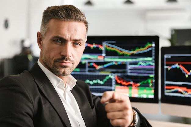 Wizerunek biznesowego mężczyzny 30-tych w garniturze pracującego w biurze na komputerze z grafiką i wykresami na ekranie
