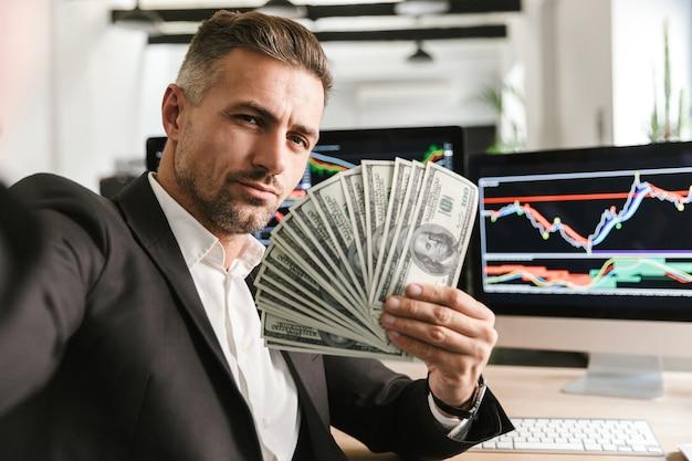 Wizerunek bogatego biznesmen 30s na sobie garnitur, trzymając wentylator pieniędzy podczas pracy w biurze z grafiką i wykresami na komputerze