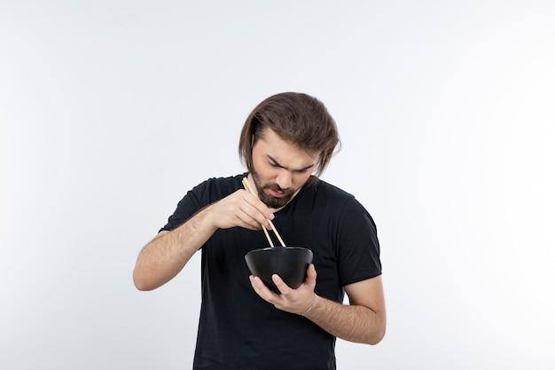 Wizerunek brodatego mężczyzny trzymającego miskę pałeczkami na białej ścianie.