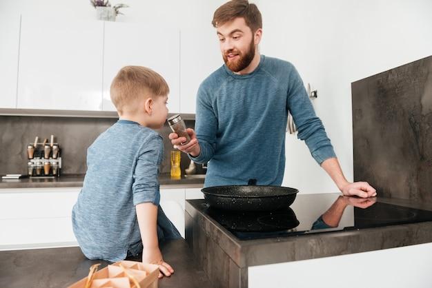 Wizerunek brodatego ojca ubranego w niebieski sweter gotującego w kuchni ze swoim małym słodkim synkiem