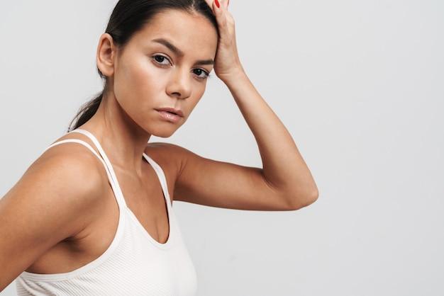 Wizerunek brunetki fitness w odzieży sportowej stojącej i patrzącej na kamerę