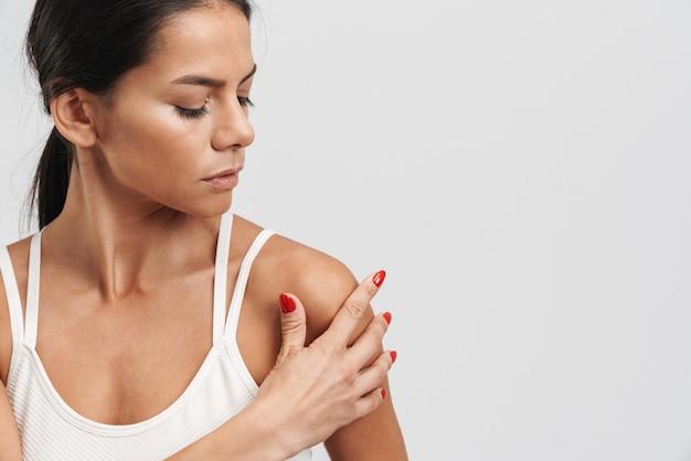 Wizerunek brunetki fitness w sportowej odzieży stojącej i dotykającej jej ramienia