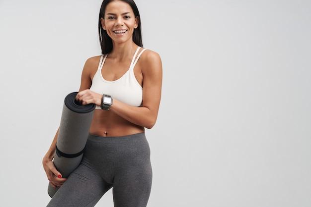 Wizerunek brunetki młodej kobiety w odzieży sportowej trzymającej matę fitness podczas treningu