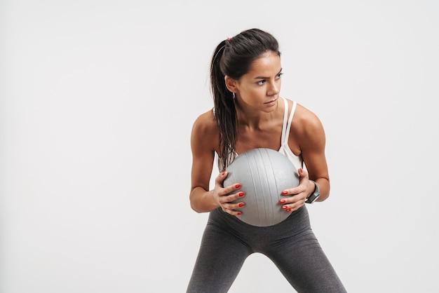 Wizerunek brunetki młodej kobiety w odzieży sportowej trzymającej piłkę fitness podczas treningu