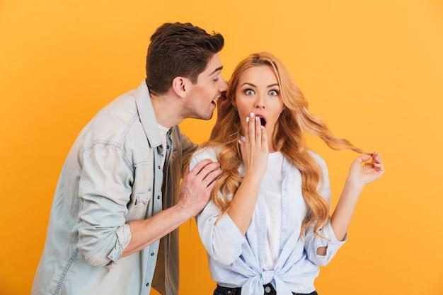 Wizerunek brunetki szepczącego jej do ucha tajemnicę lub ciekawą plotkę zaskoczonej kobiecie, odizolowany na żółtej ścianie