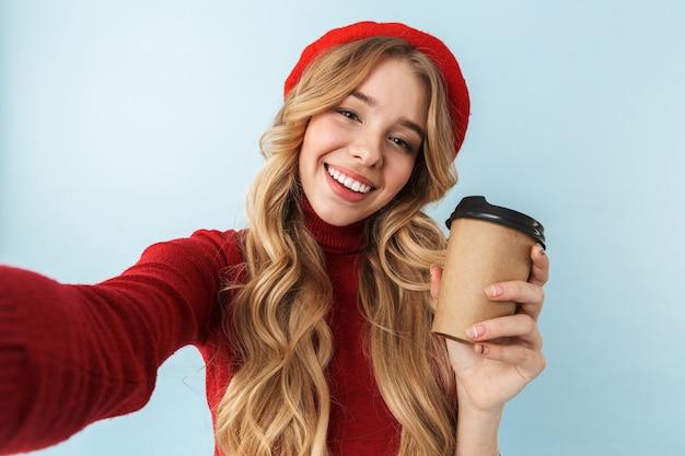 Wizerunek całkiem blond kobieta 20s sobie czerwony beret trzymając papierowy kubek z kawą podczas robienia zdjęcia selfie, na białym tle