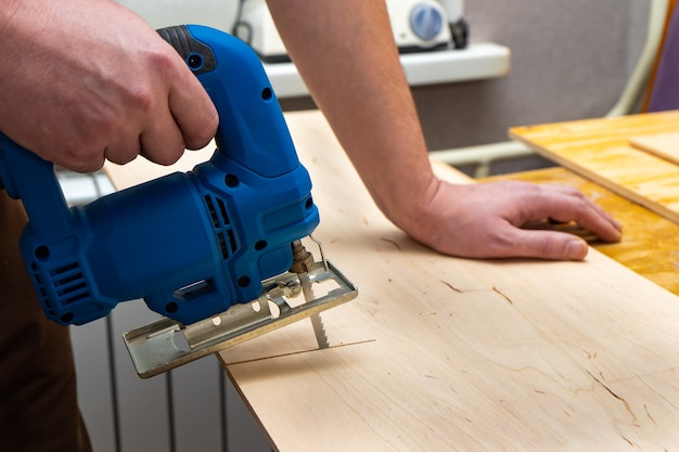Wizerunek dłoni człowieka za pomocą układanki elektrycznej. bliska proces cięcia deski.