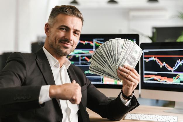 Wizerunek dorosłego biznesmena lat 30. na sobie garnitur, trzymając wentylator pieniędzy podczas pracy w biurze z grafiką i wykresami na komputerze