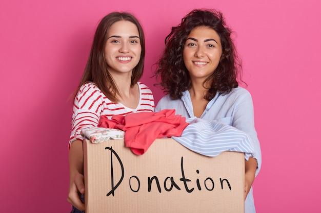 Wizerunek dwóch ładnych brunetek ubranych w czerwone paski i niebieskie koszule
