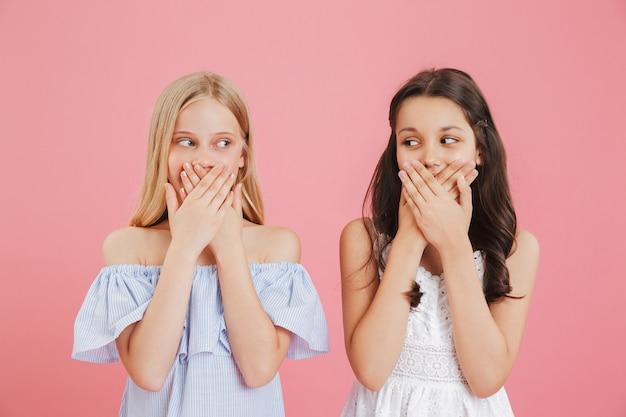 Wizerunek dwóch ślicznych dziewczyn w wieku 8-10 lat ubranych w sukienki zakrywające usta rękami i patrząc na siebie, odizolowane na różowym tle